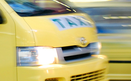 close up image of a taxi passing with its lights on.