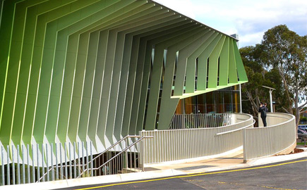 Image of the Swinburne University Wantirna campus, showing the side of a green building with students walking up ramp.