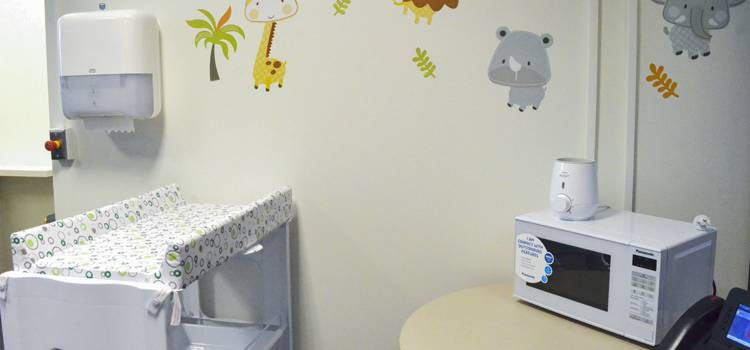 Paper towel dispenser, change table, microwave oven and fridge in the parents' room.