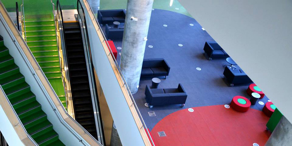 Interior image of a Swinburne University building, showing an over of escalators and waiting area with colourful seats.