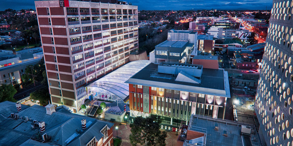 Overview image of the Swinburne Hawthorn campus at night showing the Library, Atrium and other buildings in the distance.