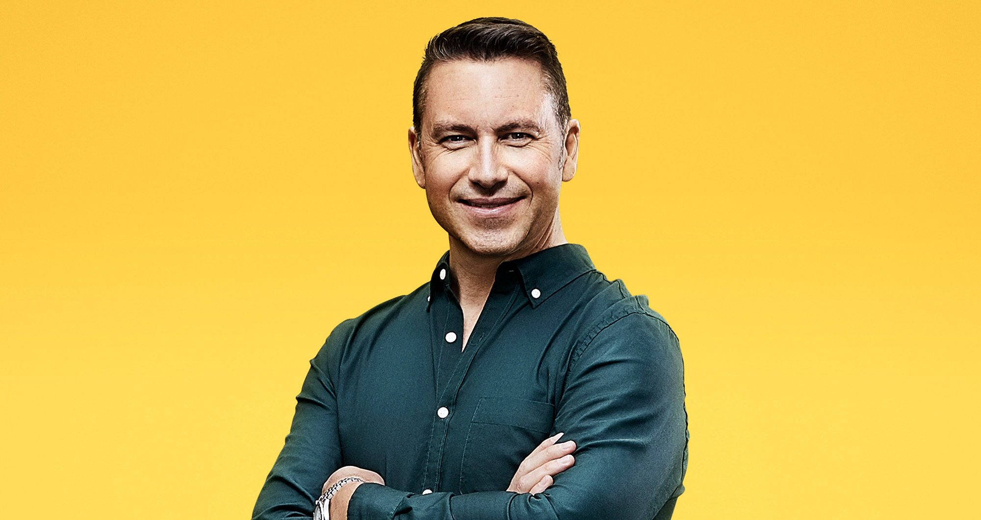 Smiling man with arms crossed, yellow background