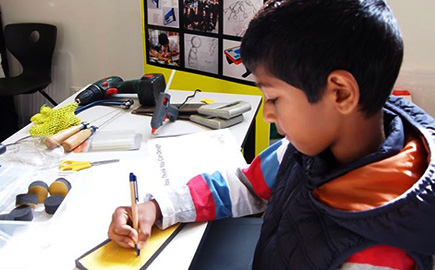Young boy drawing on a desk