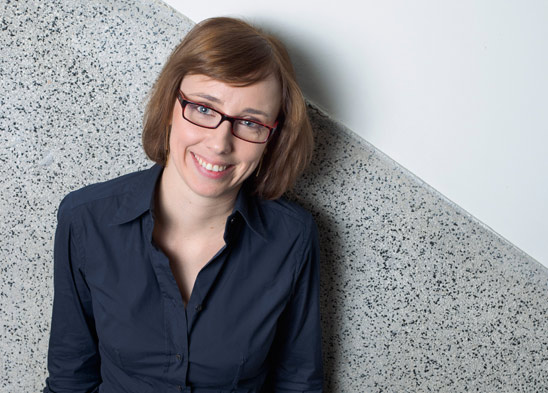 Eva is wearing a dark blue shirt and glasses. She is smiling and looking at the camera. She stands in front of a grey and dark grey background.