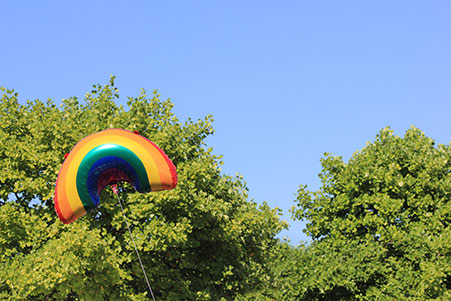 Helium filled balloon in the shape and colours of a rainbow, floating among trees.
