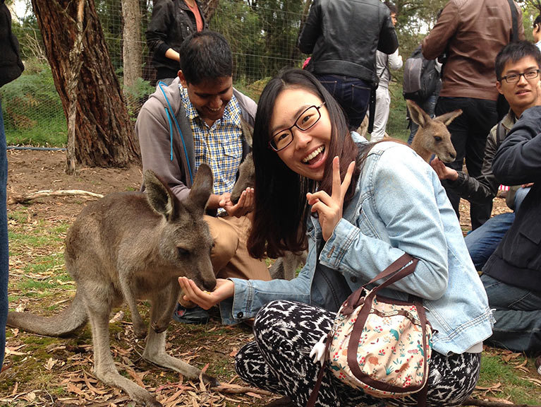 International student kneeling and feeding a wallaby in a park.