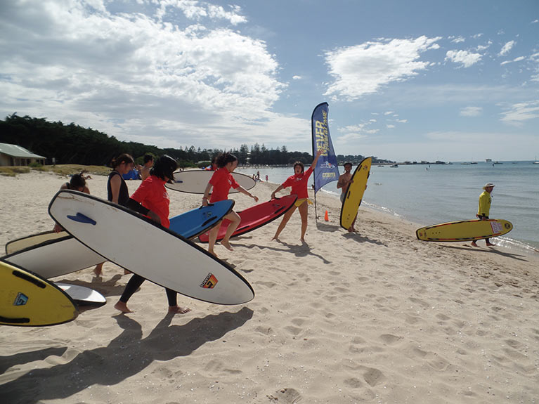 Multiple students holding surfboards walking across the sand into the beach.