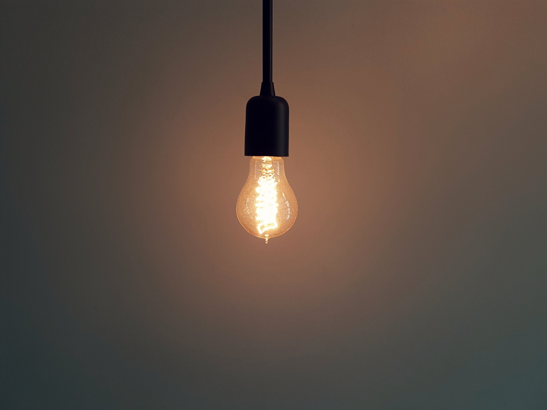 A light bulb hanging from the ceiling from a power cable, illuminating the plain background wall.