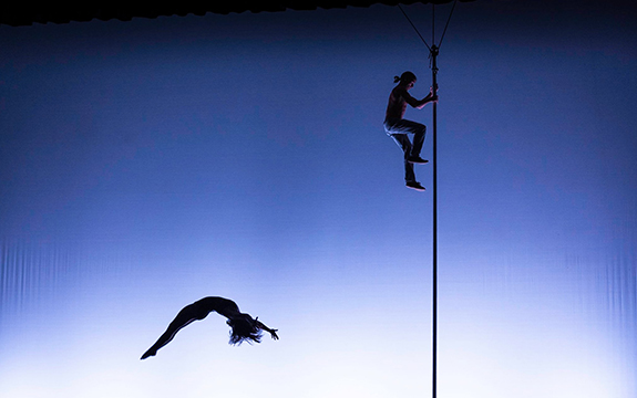 A NICA acrobat is crawling up a pole while another is jumping