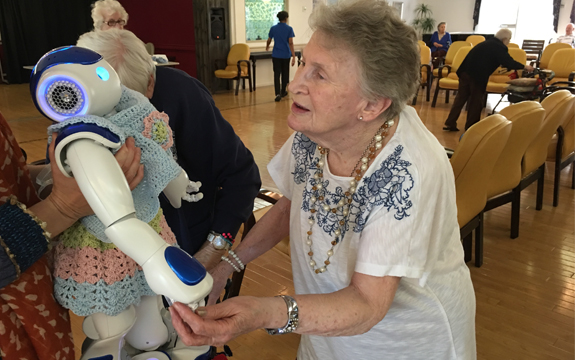 A person in an aged care home interacts with a NAO robot