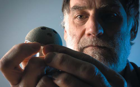 Professor Chris Berndt holding a surface engineered medical implant