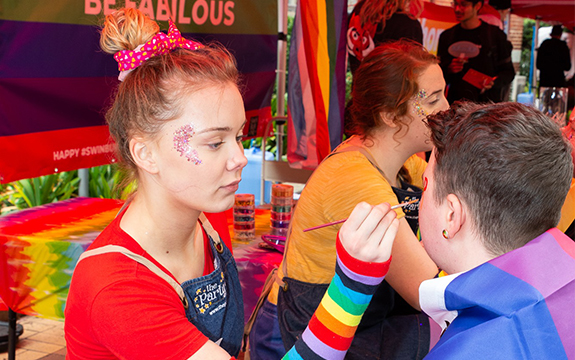A face painting paints a student's face at the Pride Fair Day