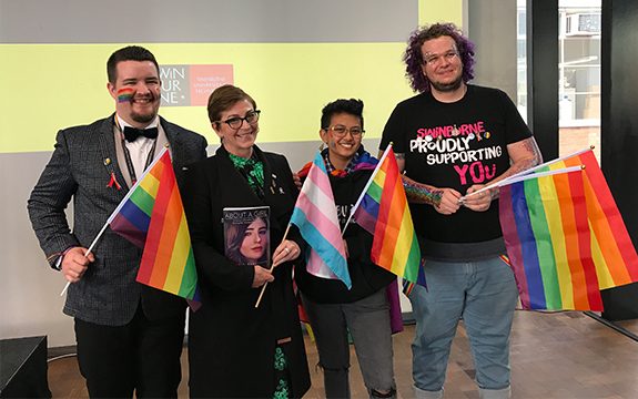 Transcend founder and Wear It Purple patron Rebekah Robertson poses with three Swinburne Queer Collective students all holding Pride Flags
