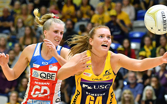 NSW Swifts goal defender and Sunshine Coast Lightning goal attacker chase after netball.