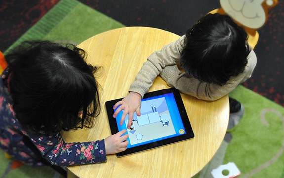 Children are sitting at a desk playing on a tablet computer