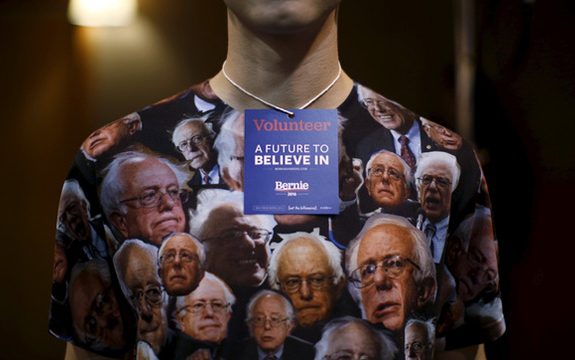 A young supporter wears shirt covered in pictures of bernie sanders and a volunteer card around their neck