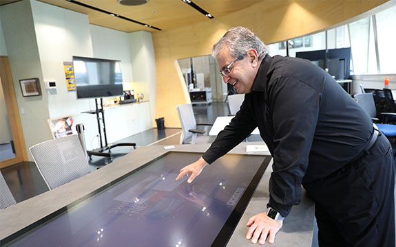 Professor Dimitrios is in the Factory of the Future at Swinburne University of Technology using an interactive touch screen