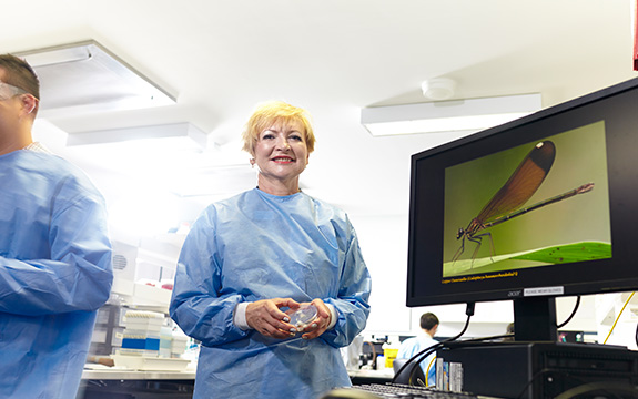 Professor Ivanova in the lab next to a screen showing a picture of a dragonfly