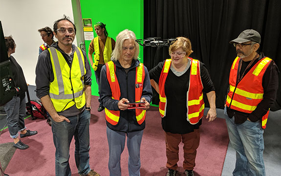 Four Swinburne staff members who are teachers are wearing hi-visibility vests and are learning how to fly a drone in a classroom