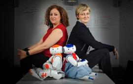 Dr Therese Keane sitting with a humanoid robot