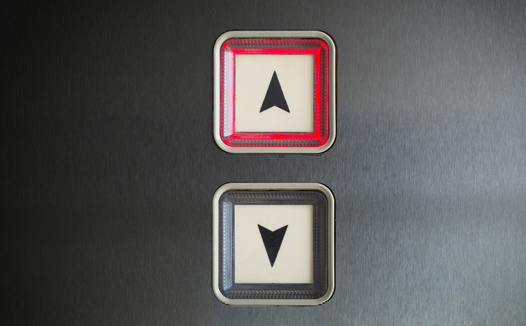 Photograph of the up and down buttons of an elevator. The up button is lighting up, indicating the elevator will be taking the user higher up.