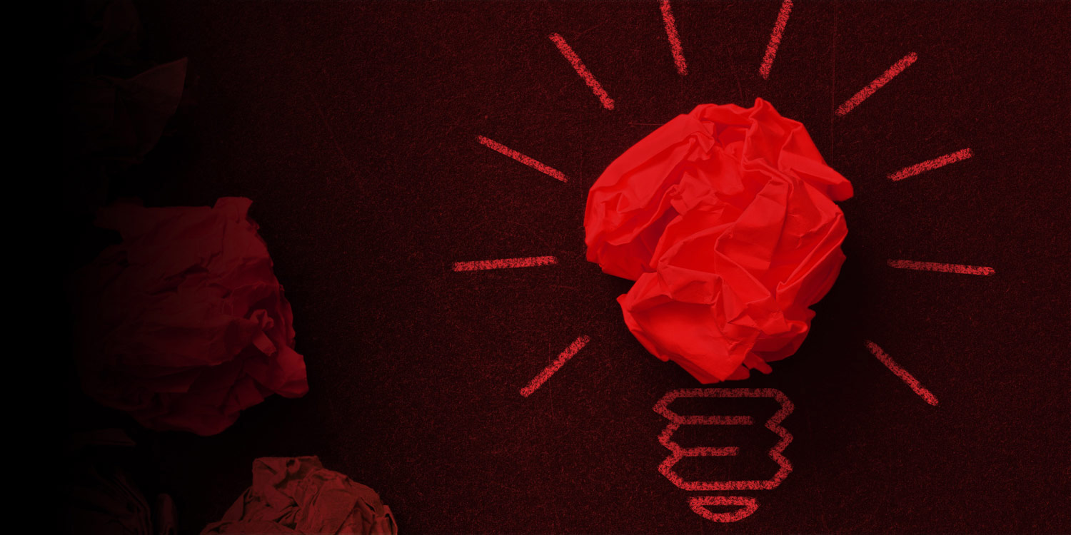 An image of a red light globe created using a scrunched paper ball for the head of the globe and chalk line drawings for the base. There are red chalk lines emanating from the globe, symbolising an idea has been discovered.