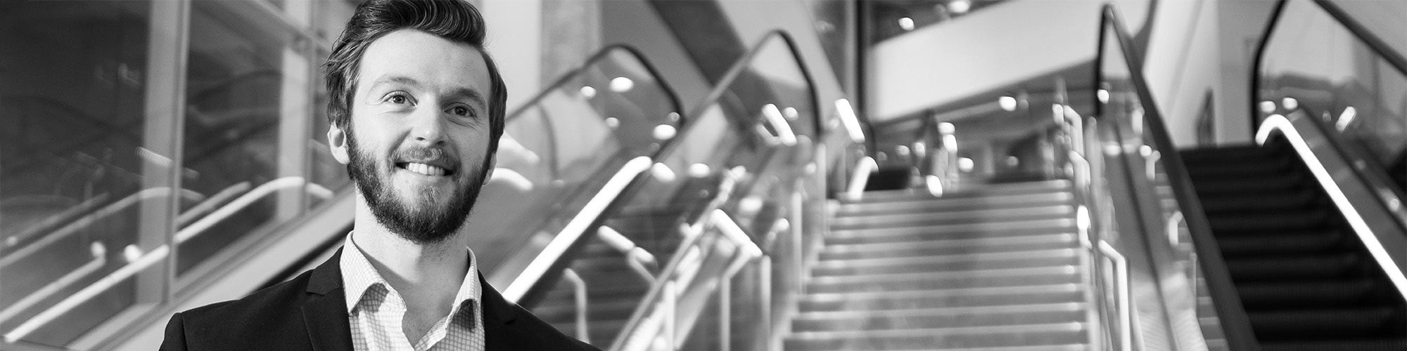 A greyscale image of a man in a suit standing inside a building lobby with escalators behind him.