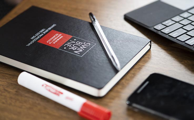 A workdesk with a Swinburne University branded notebook, pen and whiteboard marker. There are cropped parts of a laptop and mobile phone showing from the edge of the image.