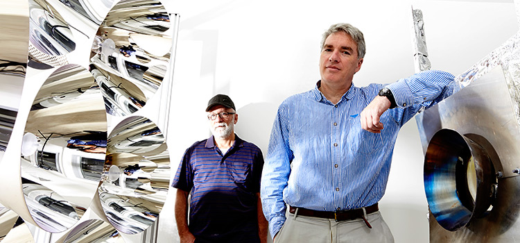 Swinburne metallurgical engineers Professor Geoff Brooks and Dr Ben Ekman with the solar simulator developed by Ekman.