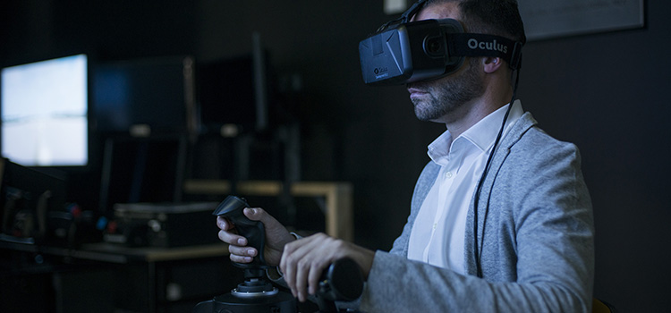 A researcher wearing virtual reality goggles uses one of Swinburne's aviation simulators