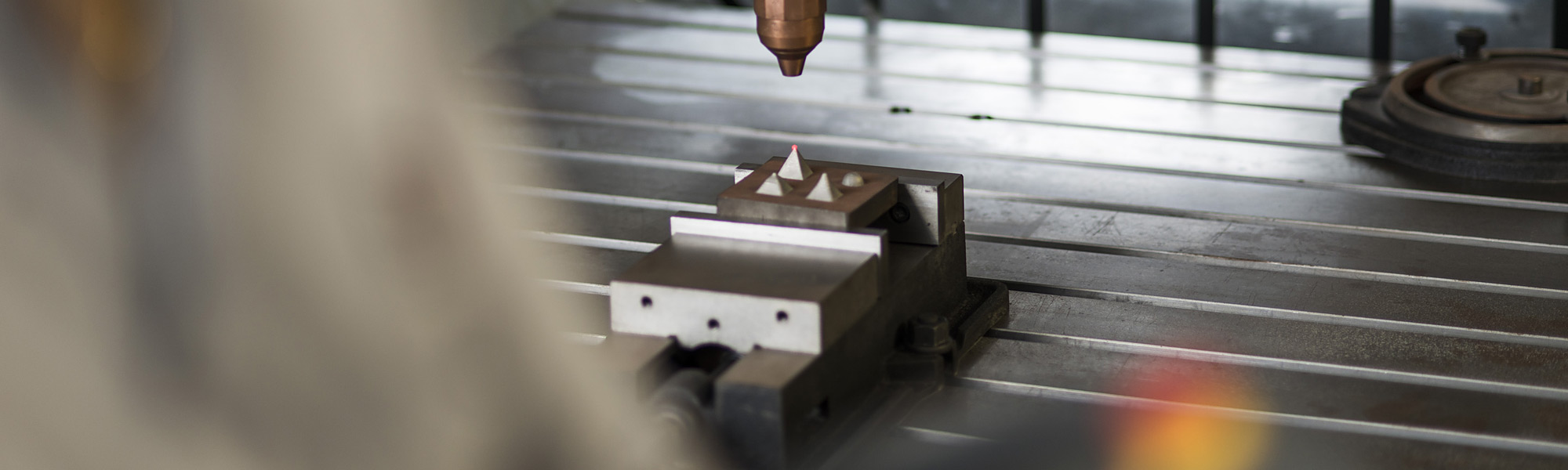 3D metal printer producing three aluminium pyramids on a metal plate with a laser pointing on one of the pyramids.