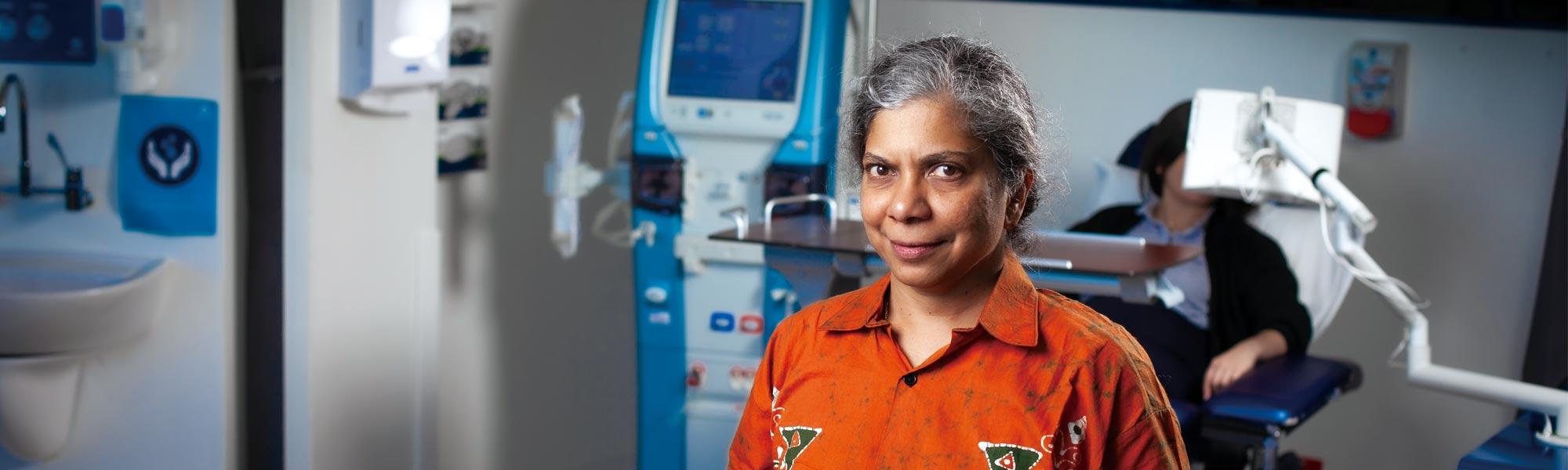 Professor Nilmini Wickramasinghe standing in a hospital with a patient getting tests whilst lying down behind her.