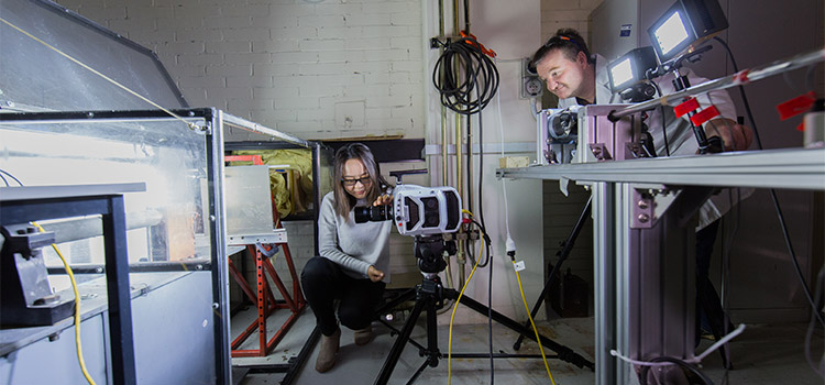 Two engineers are using a high speed camera inside a laboratory.