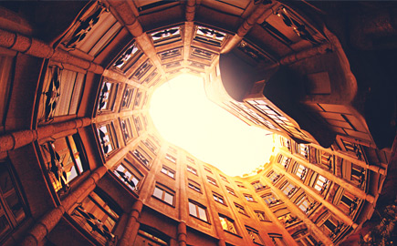 Looking up through building courtyard to sky