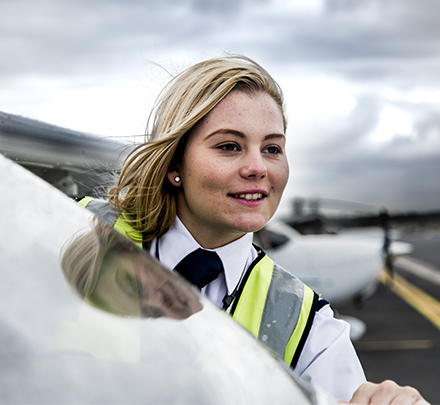 Girl in high vis stands at plane door smiling