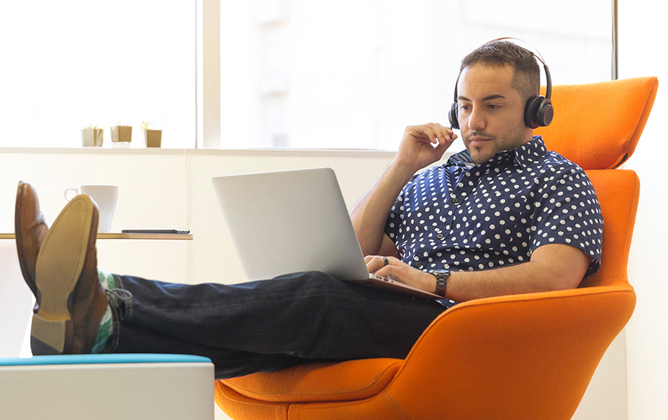 Man sitting in an orange arm chair, feet up with a laptop and headphones.