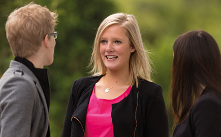 Three students are having a conversation outside. The camera focuses on a blonde lady wearing a black jacket and pink top.