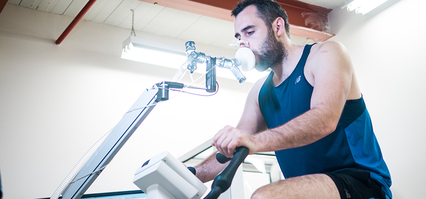 An athlete participates in a health and wellness exercise science test on a stationary bicycle in a laboratory.