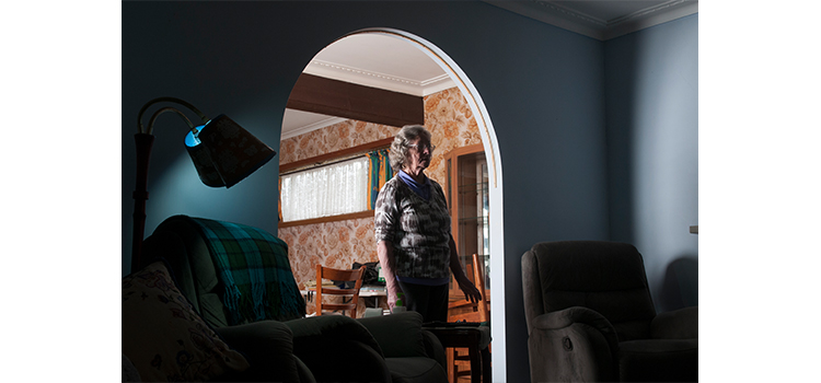 a photograph of an old lady stands in her dark living room