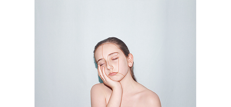 A photograph of a girl with her hand on her face against a white wall by photo imaging student Mia Milkins