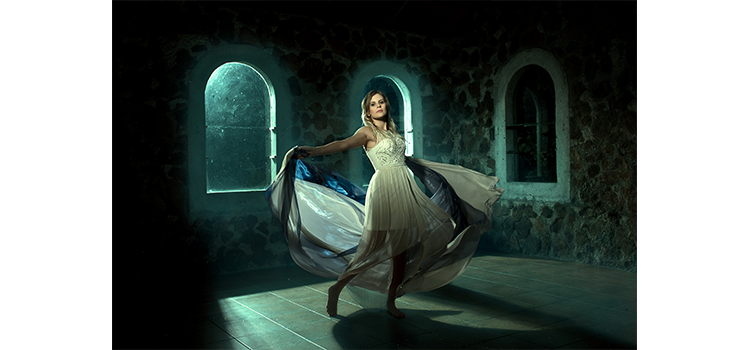 A photograph of a women in a dark building dancing in a dress by student Kade Cumming