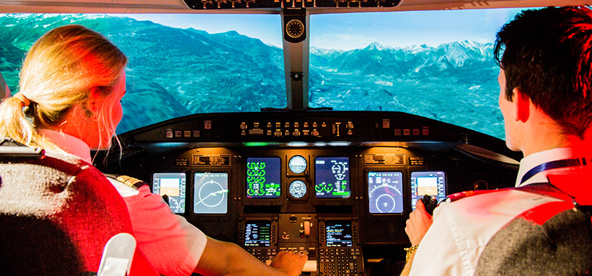 Aviation students sit in the cockpit of a flight simulator overlooking mountains.