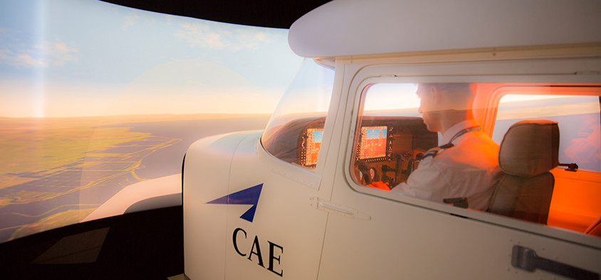 An aviation student pilots a flight simulator.