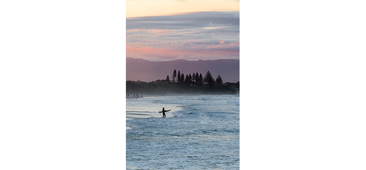 Photography student Gina Clement's photographs a surfer heading into the water with a city landscape in the background