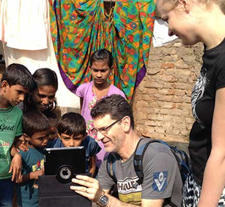 Photograph of staff member and student with children in India