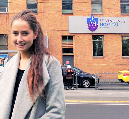 Psychology and psychophysiology professional placement student Isabella Close stands in front of St Vincent's Hospital in Melbourne.