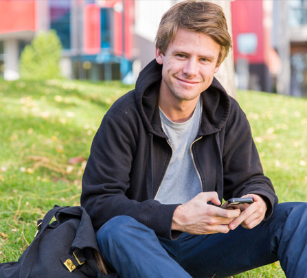 Jamie, an advertising student at Swinburne, sits on the lawn of Wakefield Gardens holding his phone.
