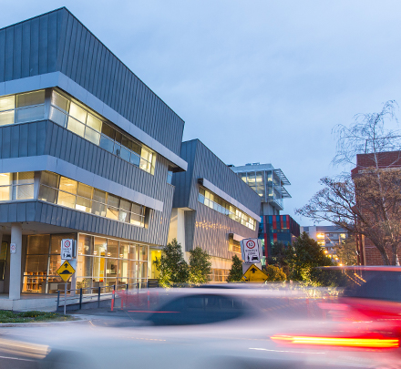 The Australian Graduate School of Entrepreneurship building at Swinburne University of Technology's Hawthorn campus is lit up at night as cars drive past.