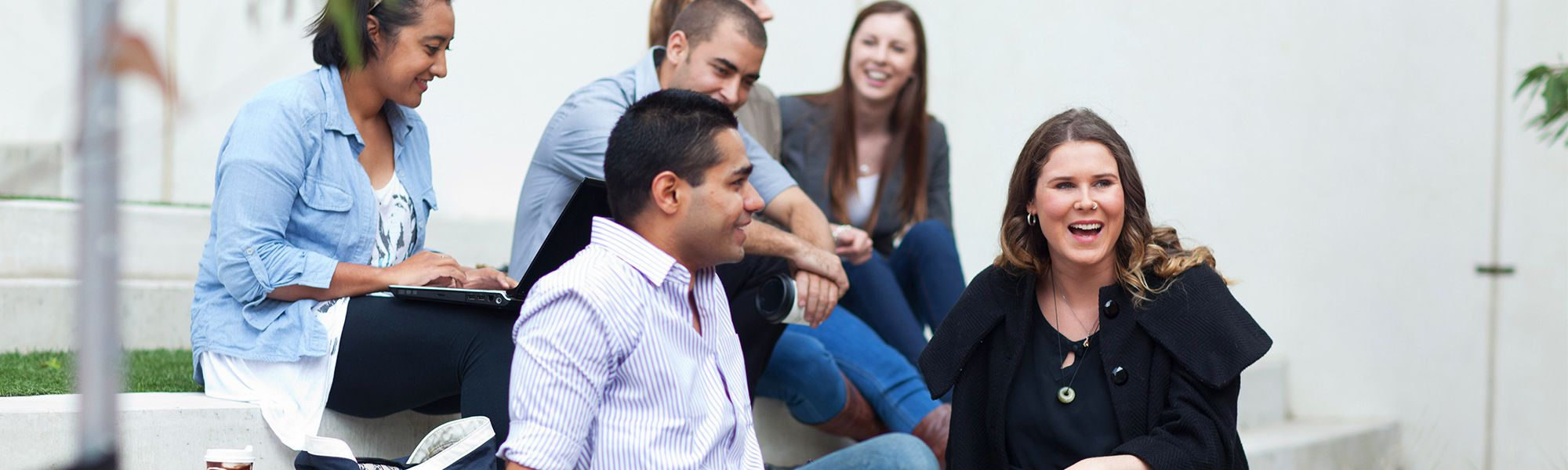 A group of six students are sitting outside having a conversation. Two students are in focus with four in the background.