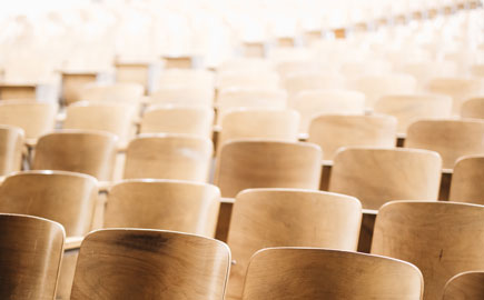 A view of an empty light filled lecture theatre with wooden chairs.